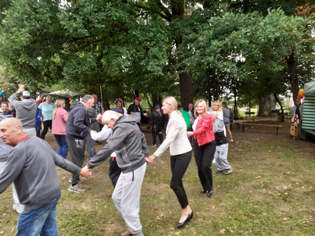Grupa mieszkańców wraz z Dyrektorami bawi tańczy w kółku trzymając się za ręce.