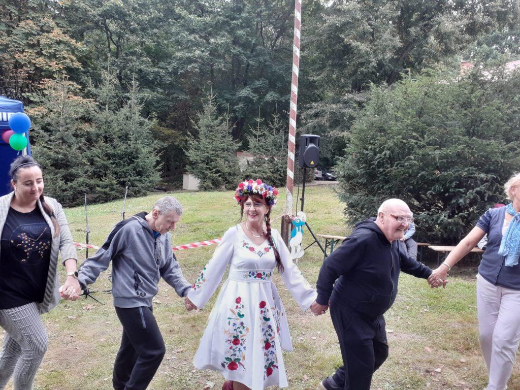 Kobieta z zespołu folklorystycznego ubrana w barwy Kociewia trzyma się za ręce i tańczy z mieszkańcami