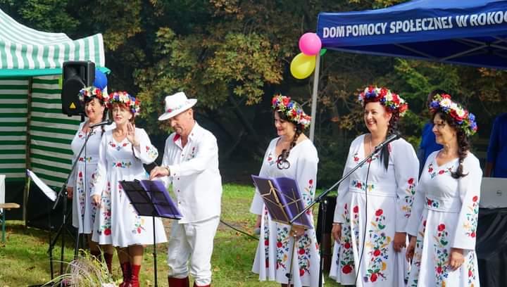 Pięć kobiet ubranych w folkowe stroje oraz mężczyzna z białym kapeluszem stoją przed śpiewnikami i mikrofonami. Razem śpiewają