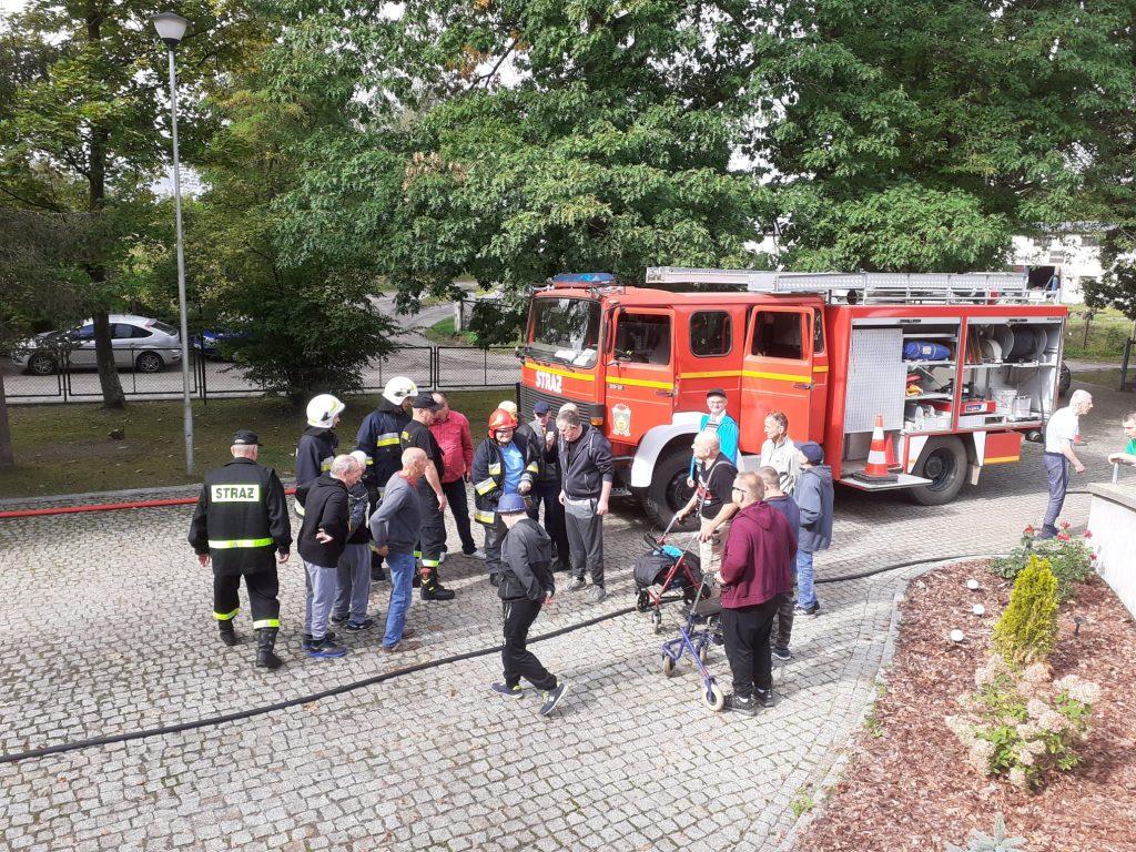 Wóz strażacki na podjeździe do siedziby Domu a przy nim strażacy oraz zainteresowani podopieczni Domów.