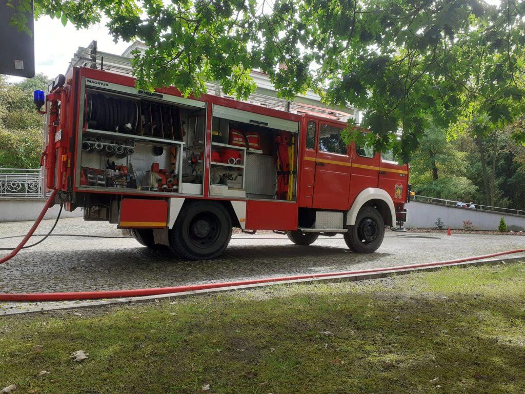 Wóz strażacki z otwartymi bocznymi przegrodami. W środku węże oraz osprzęt.