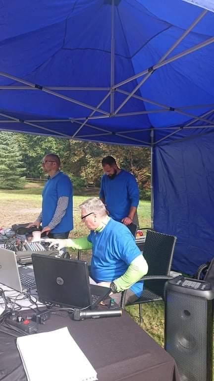 Niebieski metalowy namiot a pod nim trzech mężczyzn, którzy obsługują różny sprzęt w tym laptopy, konsolę do dźwięku i mikrofony
