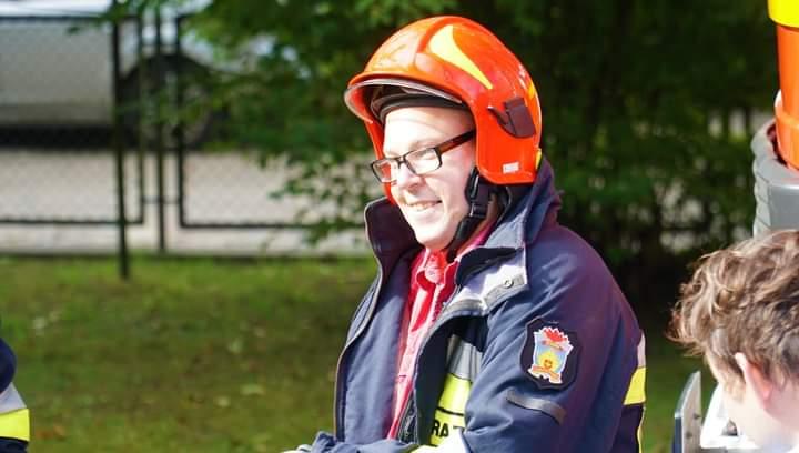 Podopieczny DPS Rokocin w kurtce strażackiej i kasku uśmiecha się