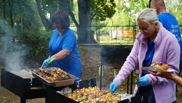 Dwie kobiety w niebieskich rękawiczkach grillują szaszłyki dla gości