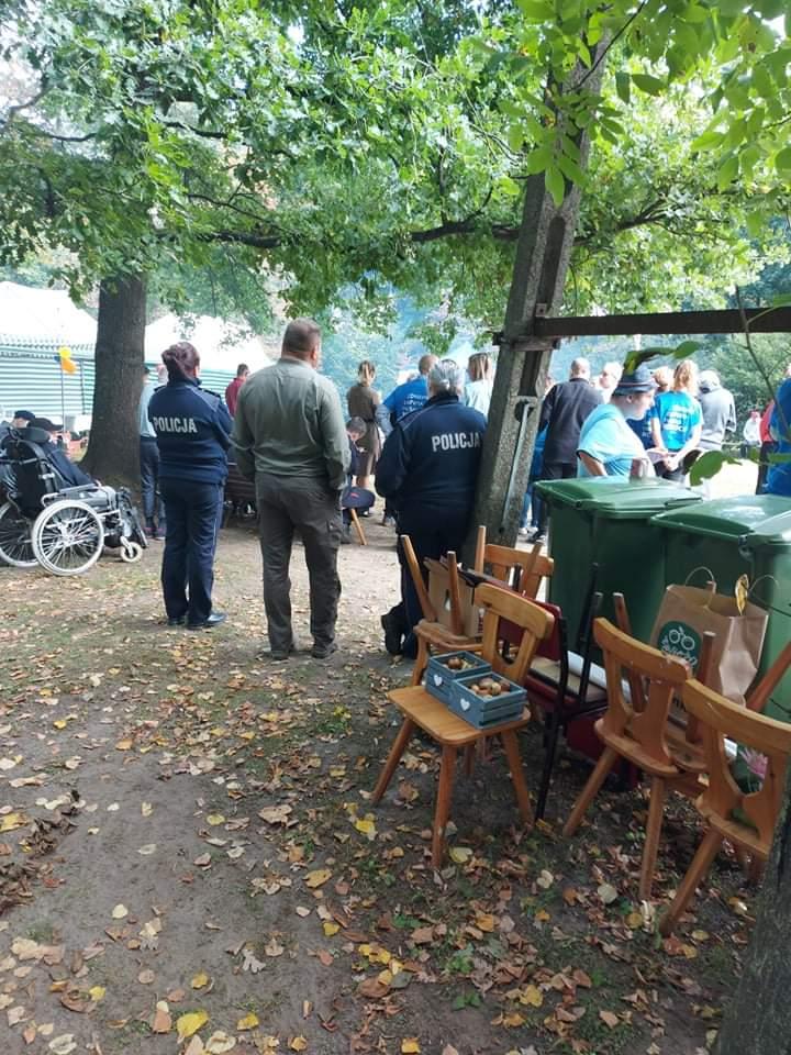Dwie policjantki stoją z boku drzewa wpatrują się w tłum ludzi.