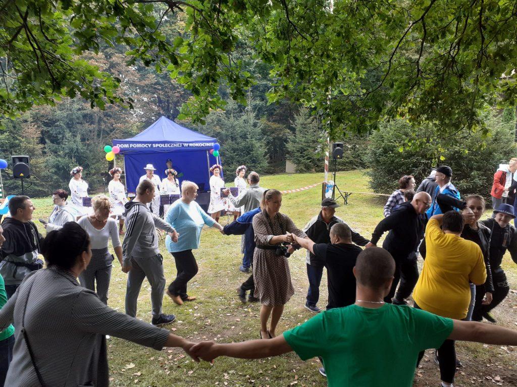 Grupa ludzi trzymając się za ręce tańczy w kółku. Z tyłu zespół folklorystyczny śpiewający