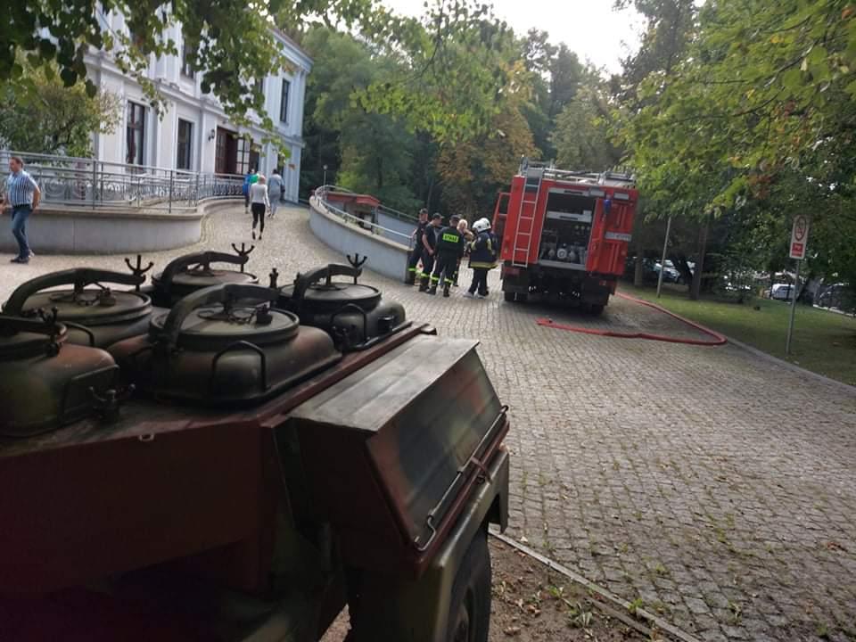 Kuchnia polowa za nią duży wóz strażacki stojący obok siedziby głównej DPS.