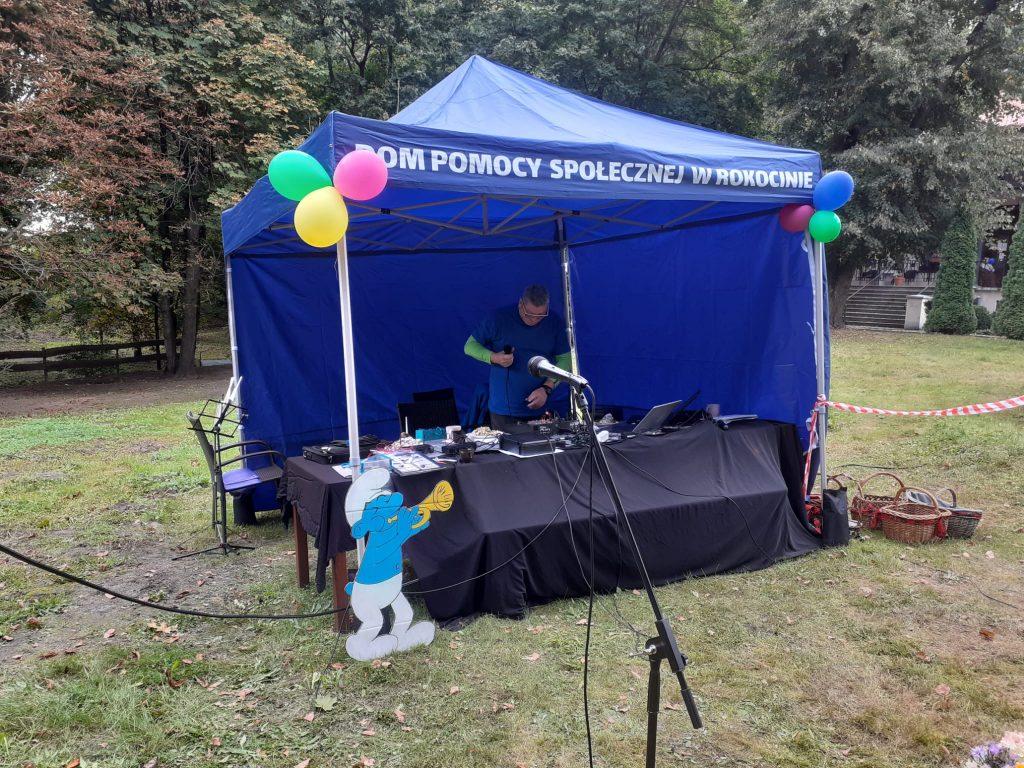 Pod niebieskim namiotem mężczyzna trzyma mikrofon i spogląda na stół w tle drzewa. Przed namiotem stojący czarny mikrofon