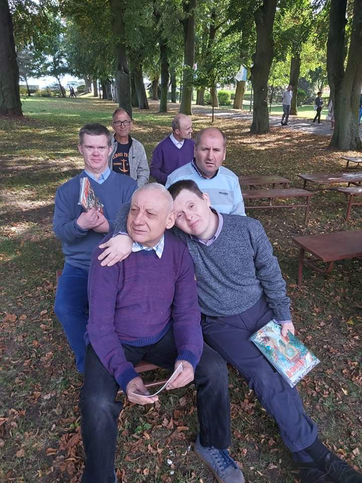 Grupa mieszkańców siedzących na ławce w parku. W koło zielono i drzewa