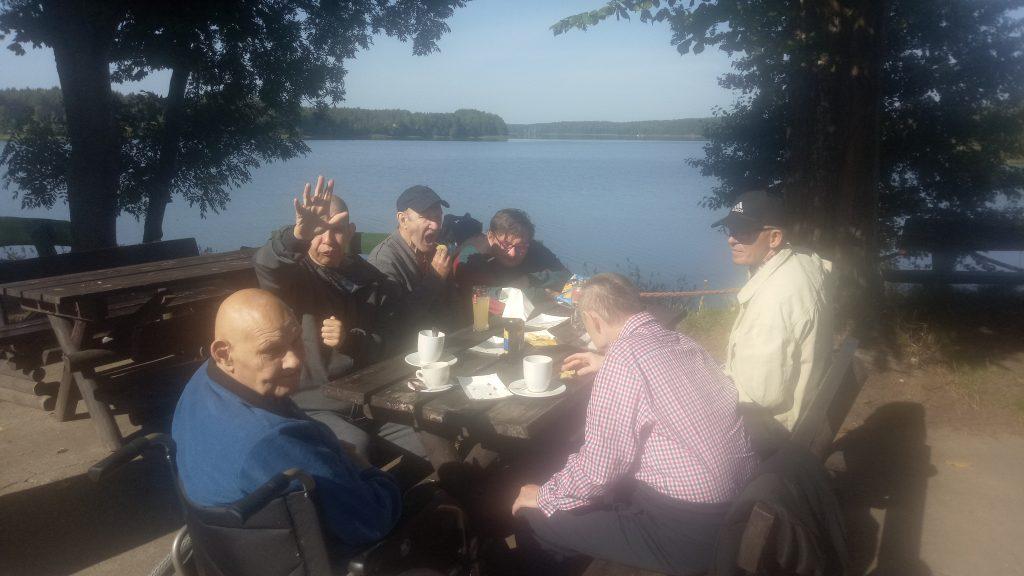 Grupa mieszkańców siedzi na drewnianej ławce niedaleko jeziora. Jedzą oraz piją kawę.