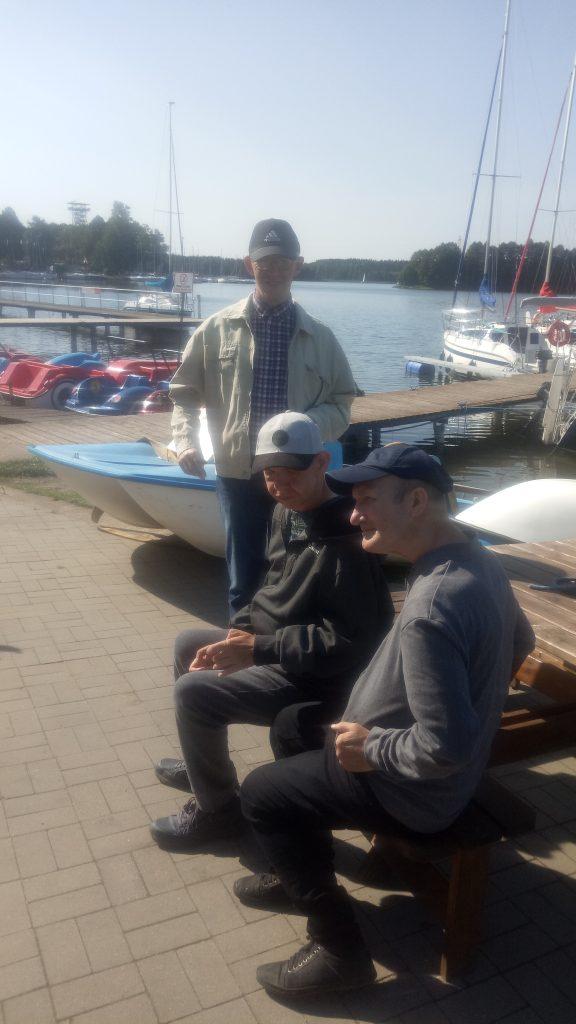Trzech mężczyzn znajduje się niedaleko jeziora w tle widać łódki i rowery wodne