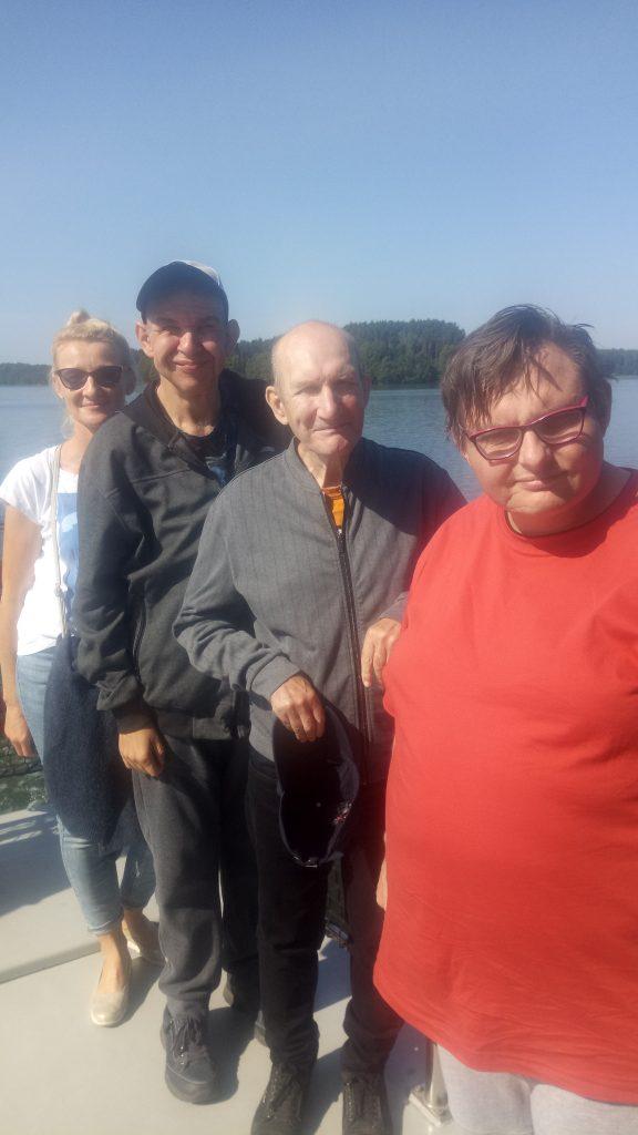 Trzech podopiecznych stoi gęsiego na łódce za nimi opiekunka, w koło otacza ich jezioro na niebie jest bezchmurne niebo.