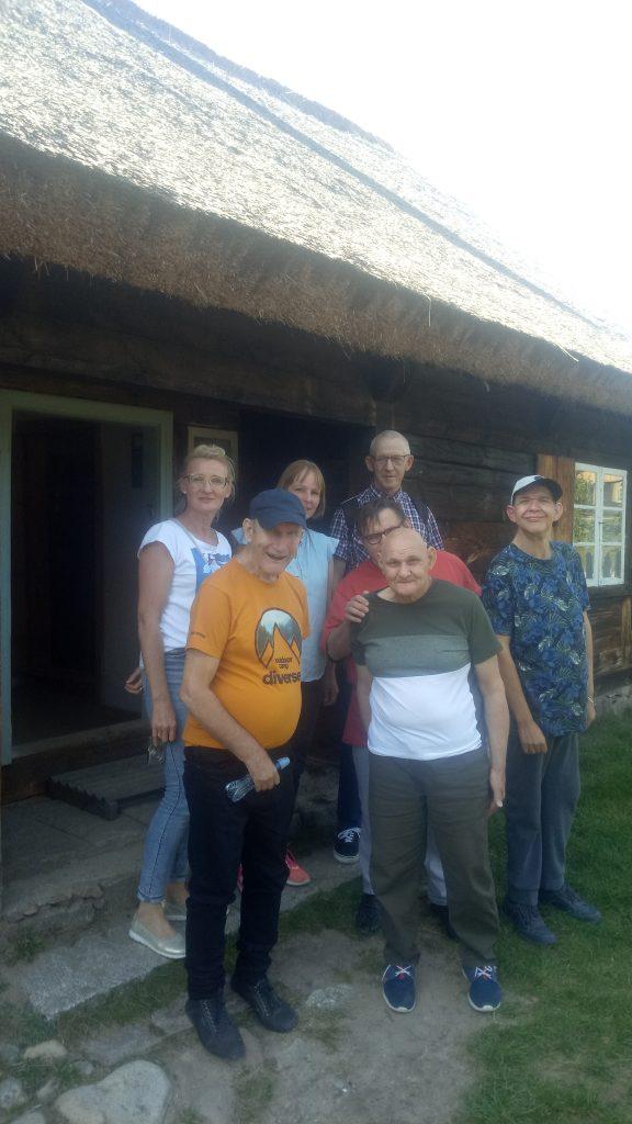 Wszyscy razem stoją pod dachem ze strzechy (słomki drewniane). Stoją przy drewnianym domu.