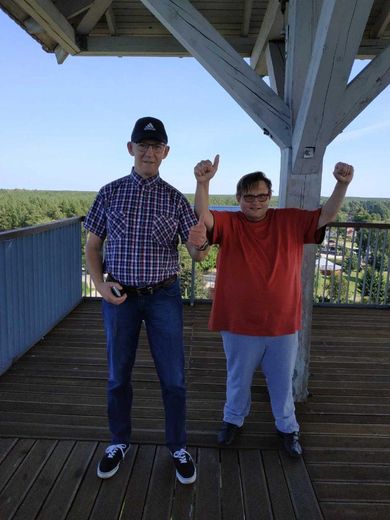 Dwóch mieszkańców unosi kciuki w górę. Stoją na szczycie drewnianej wieży.