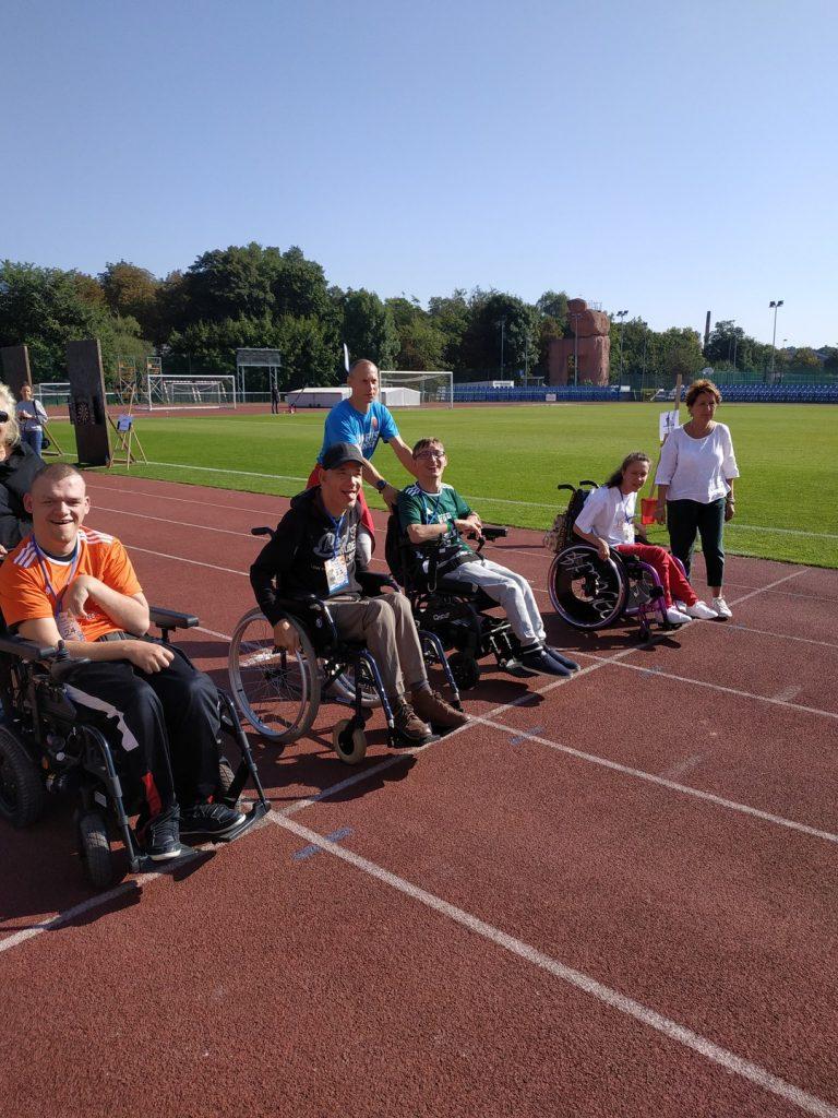 Osoby na wózkach inwalidzkich ustawione są obok siebie na bieżni na stadionie miejskim.