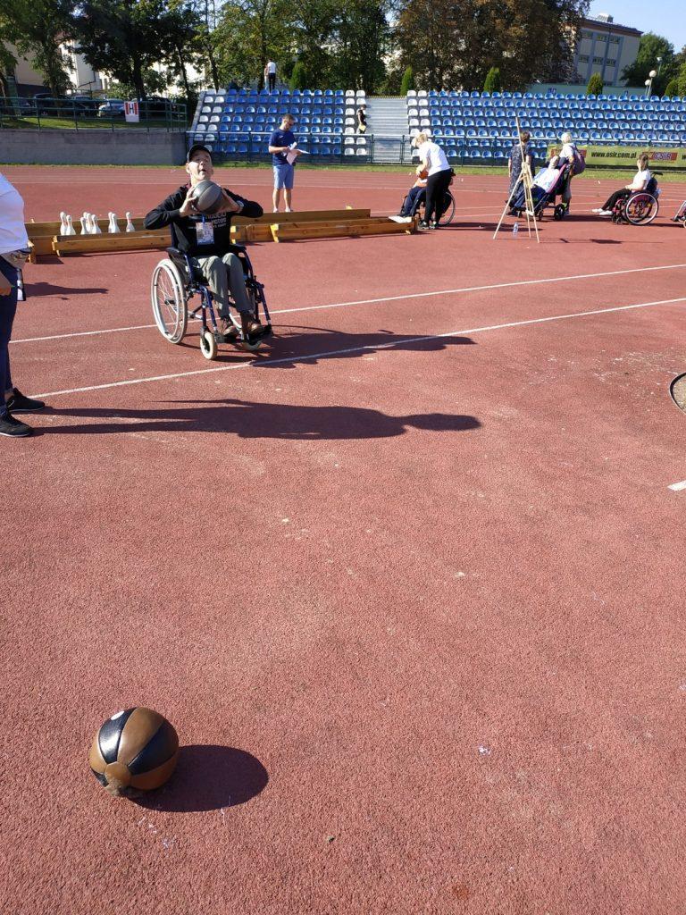 Mężczyzna na wózku inwalidzkim rzuca małą piłką lekarską na odległość