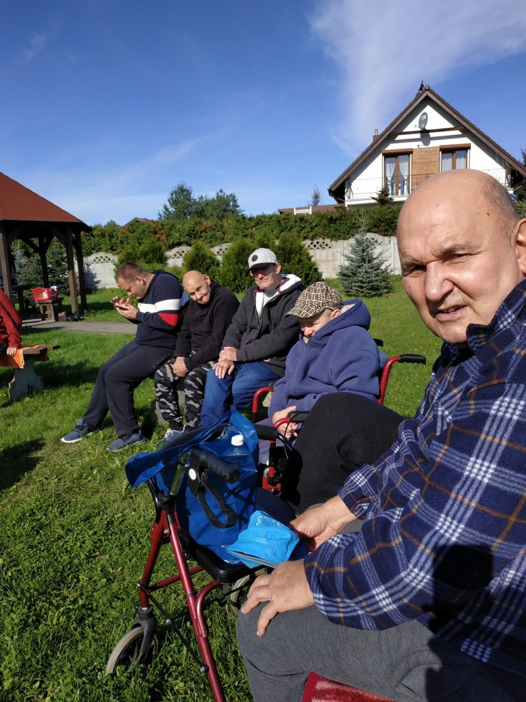 Pięciu mężczyzn siedzi przy ognisku. Jeden patrzy w stronę osoby, która zrobiła zdjęcie. Na niebie piękne niebieskie niebo