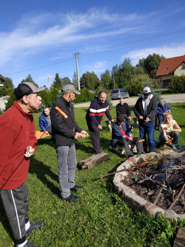 Grupa osób stoi nad rozpalonym ogniskiem, w ręce trzymają kije z kiełbaskami