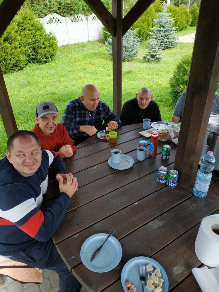 Czterech mężczyzn siedzi przy okrągłym drewnianym stole w oczekiwaniu na jedzenie