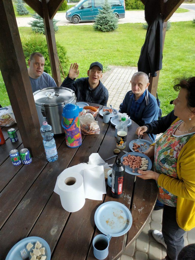 Na drewnianym stole stoją wody, termos, garnek, ręczniki papierowe, przy stole siedzi trzech mężczyzn, jeden kiwa. Obok opiekunka nakłada sałatkę