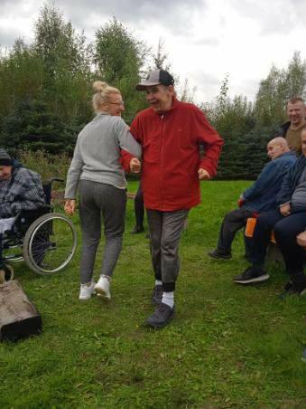 Podopieczny tańczy na zielonej trawce z opiekunka, w tle inni przyglądający się mężczyźni