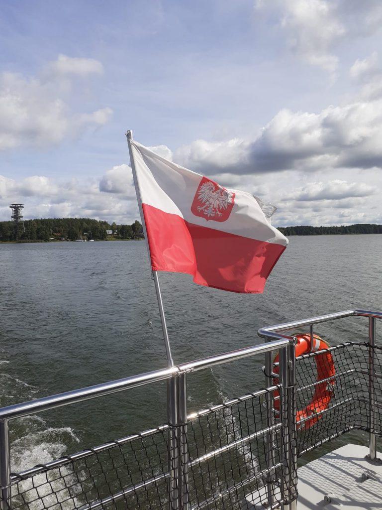 Przymocowana do statku biało czerwona flaga z godłem powiewa na wietrze.