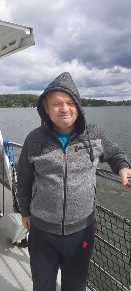Mężczyzna oparty o barierkę na statku. Za nim jezioro