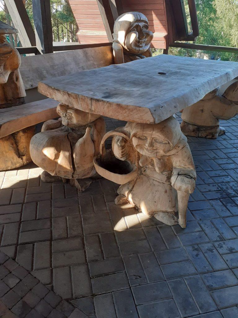 Drewniany stół, po jednej ze stron nóżki stołu przedstawiają starszą kobietę z koszykiem i chustą na głowie.