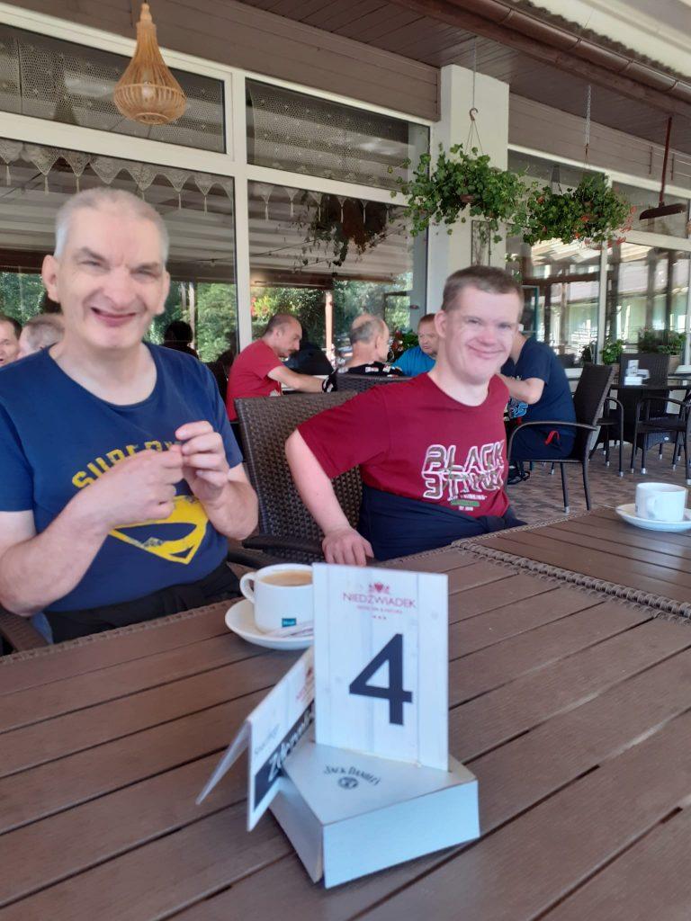 Dwóch uśmiechniętych mężczyzn siedzi przy stole. W tle inni mieszkańcy oraz duże przeszklone szyby restauracji