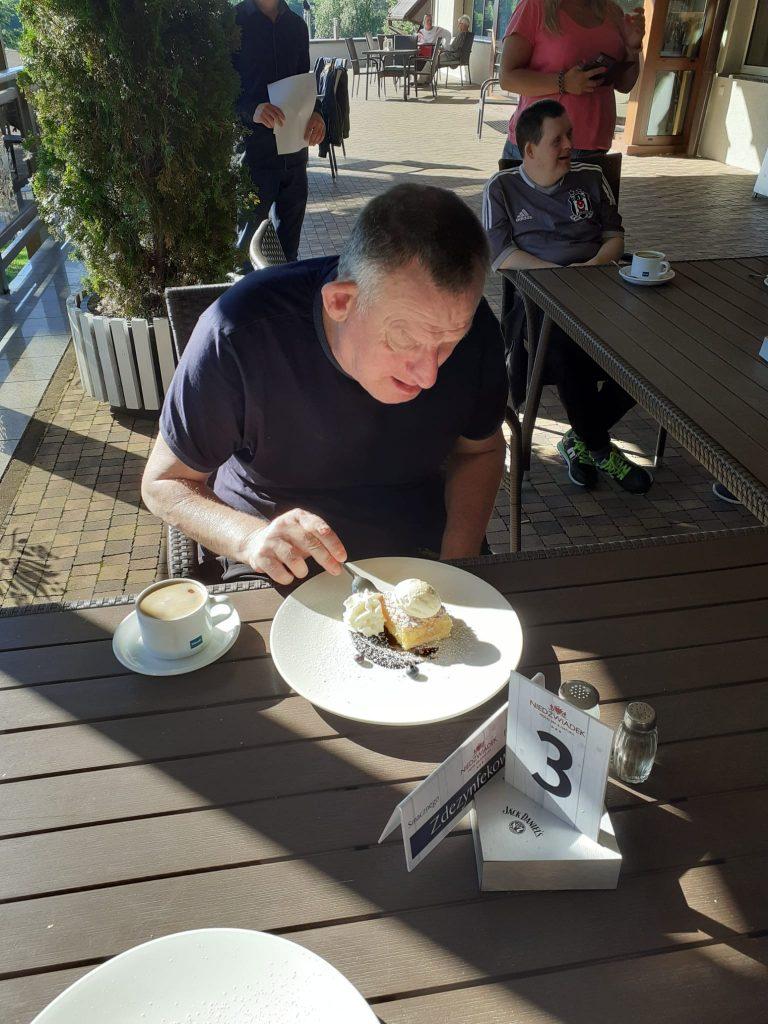 Mieszkaniec siedzący przy stole, je deser i pije kawę.