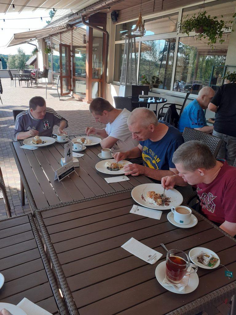 Mieszkańcy podczas posiłku w restauracji. Siedzą na dworze jedząc obiad, popijając kawą lub herbatą w tle wejście do restauracji.