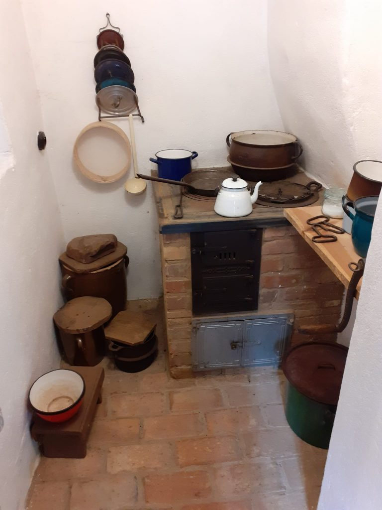 Gliniane garnki z pokrywkami na podłodze wyłożonej dużymi cegłami w rogu stary piec wraz z naczyniami
