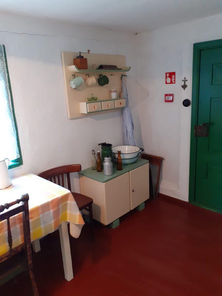 Stół z kolorową ceratą, dwa ciemne drewniane krzesła oraz szafka na której stoją butelki szklane oraz miski metalowe. Na ścianie zawieszone kubki i