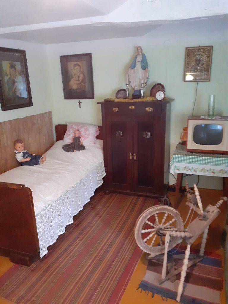 Niewielki pokój w starodawnym stylu. Ciemna komoda, obrazy dzieci oraz matki Boskiej na ścianie, łóżko z dwiema lalkami oraz stary mały telewizor na stoliku