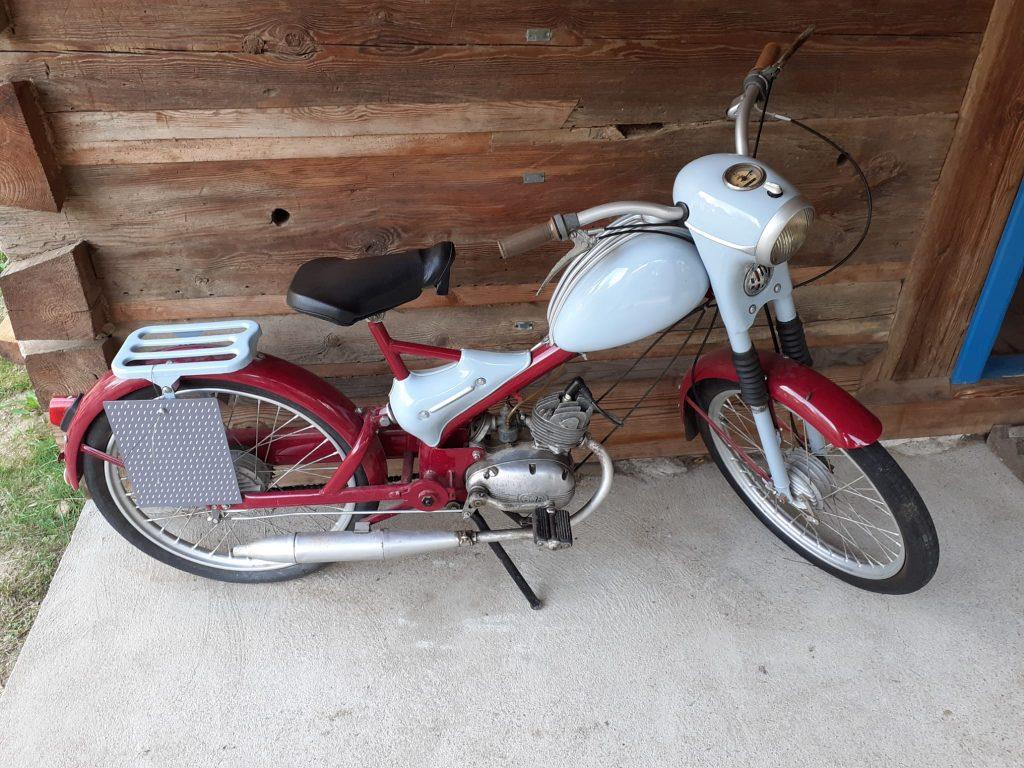 Stary biało czerwony motorower stojący na stópce.