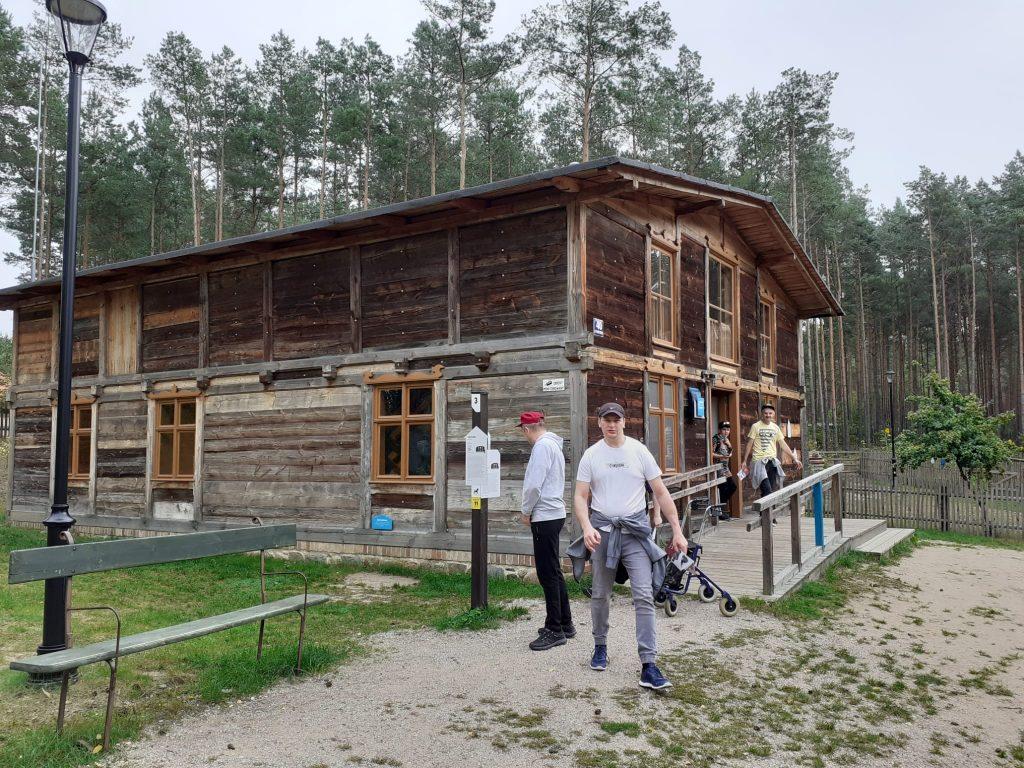 Drewniany piętrowy budynek, z którego wychodzą mieszkańcy kończący zwiedzanie. Za budynkiem las.