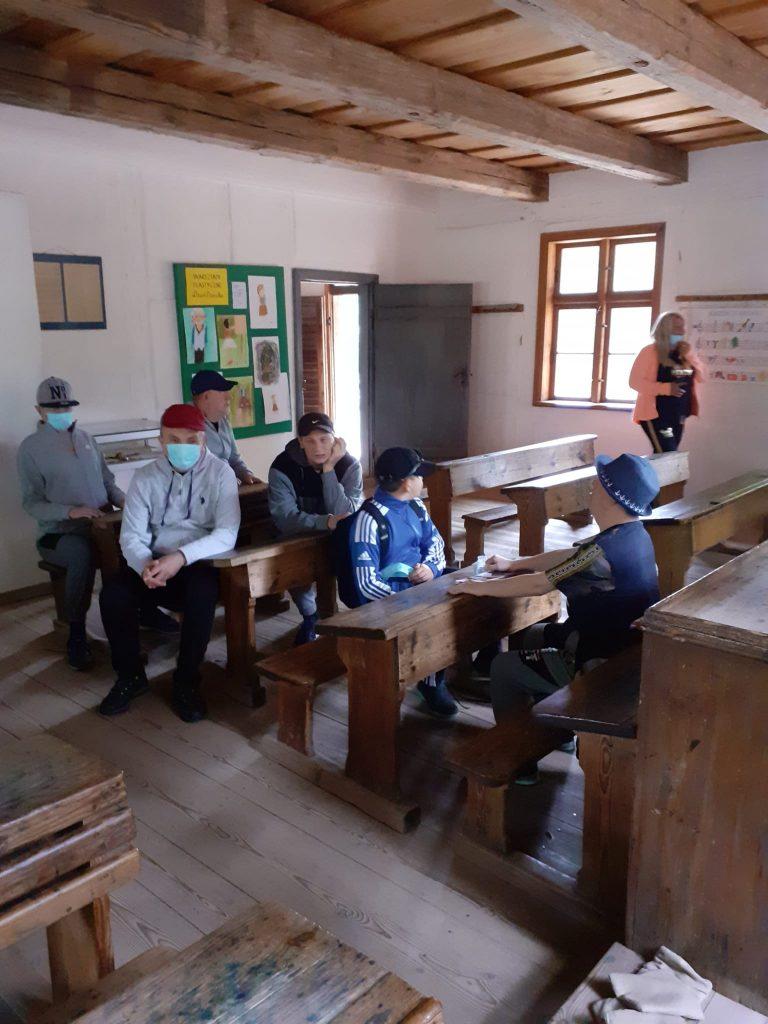 Mieszkańcy siedzący w ławkach w starym kościółku.