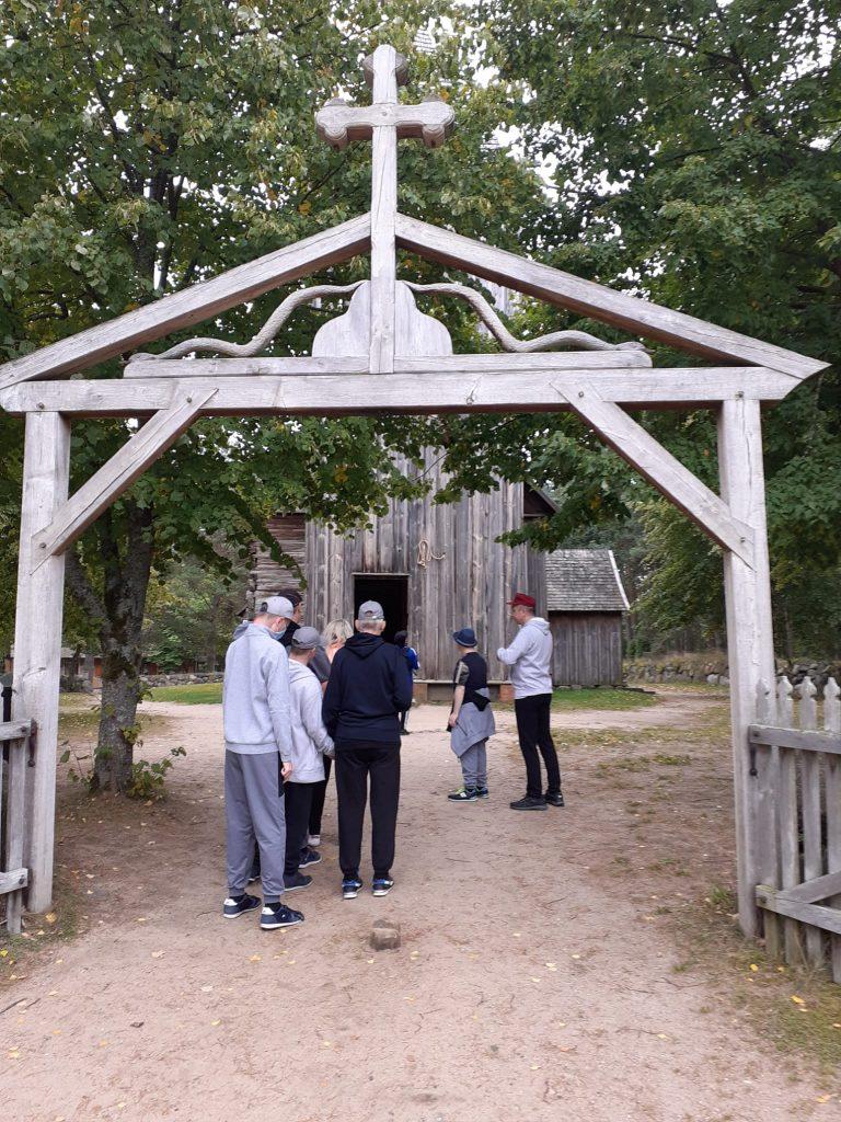 Grupa osób idąca w stronę starego drewnianego kościoła. Przed kościołem Drewniana konstrukcja (brama) z żłobionymi wzorami i krzyżem
