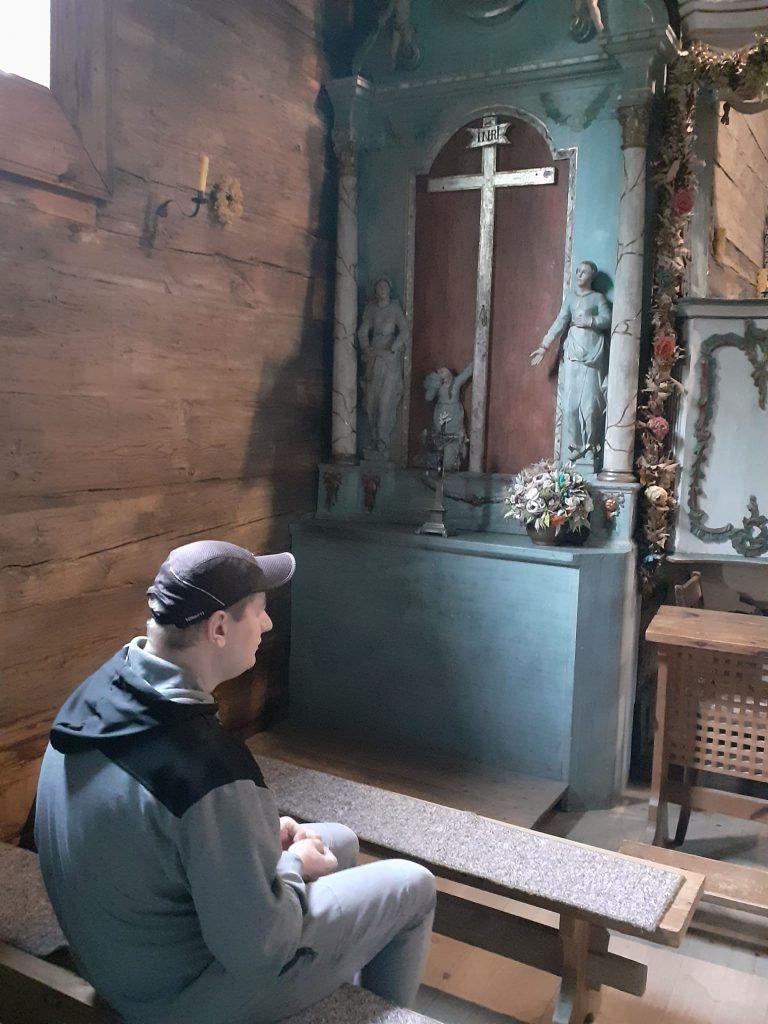 Mieszkaniec siedzący na drewnianej ławce przed krzyżem i figurkami