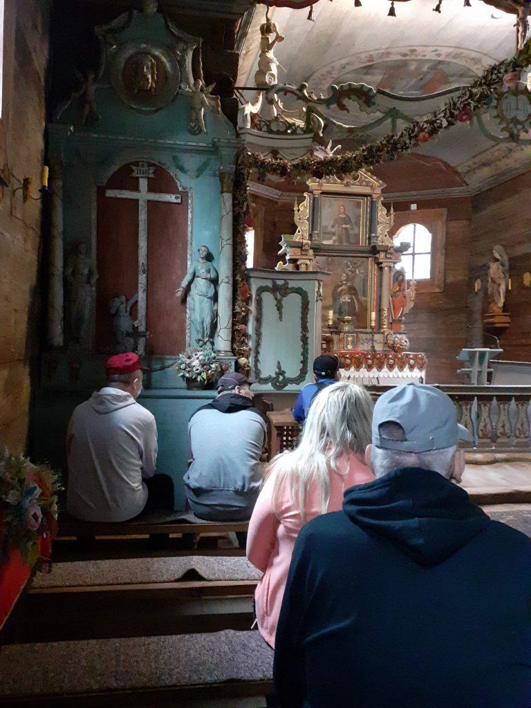 5 osób siedzących z boku ławek w starym kościele. Przed nimi ołtarz, krzyż i różne Boskie figury