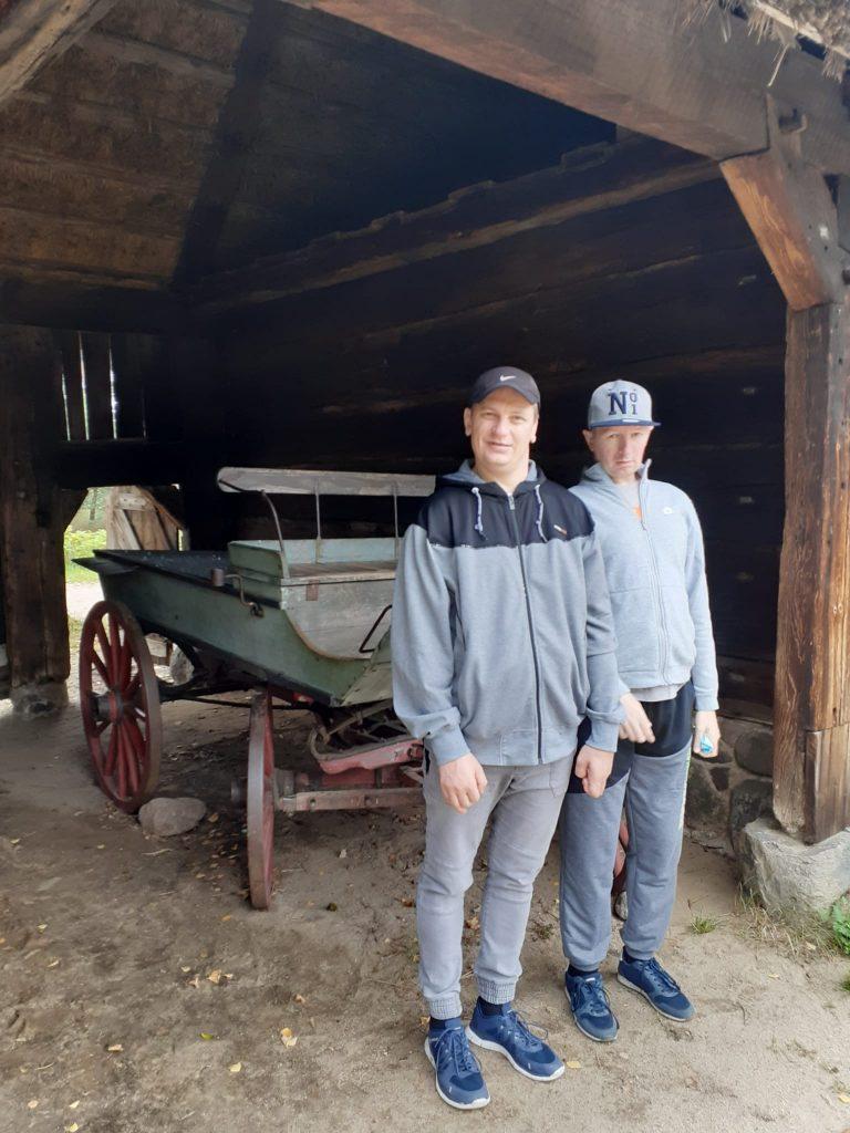 Dwóch mieszkańców stojących przed starym drewnianym wozem
