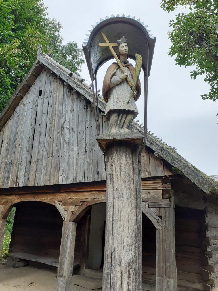 Drewniany domek ,a przed nim na drewnianym palu kapliczka z postacią trzymającą krzyż.