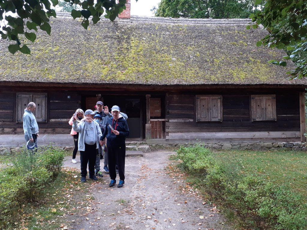Grupa mieszkańców idąca ścieżką, w tle stary drewniany dom, na dachu pokryty strzechą