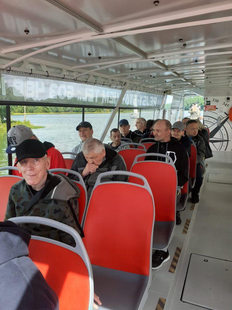 Mieszkańcy siedzący na czerwonych krzesłach w środku statku rejsowego