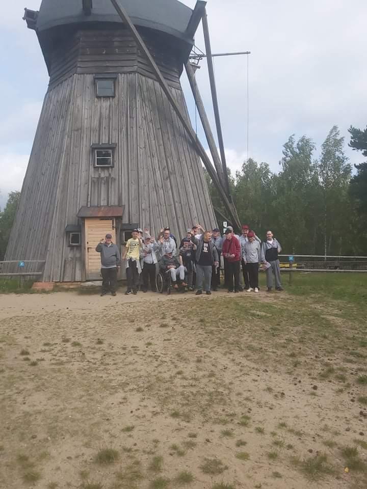 Grupa osób, która stoi pod drewnianym młynem. Część osób kiwa