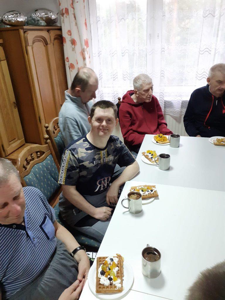 Pięciu mieszkańców siedzących przy stole, każdy z nich ma przed sobą gofra z bitą śmietaną i owocami oraz kawę.