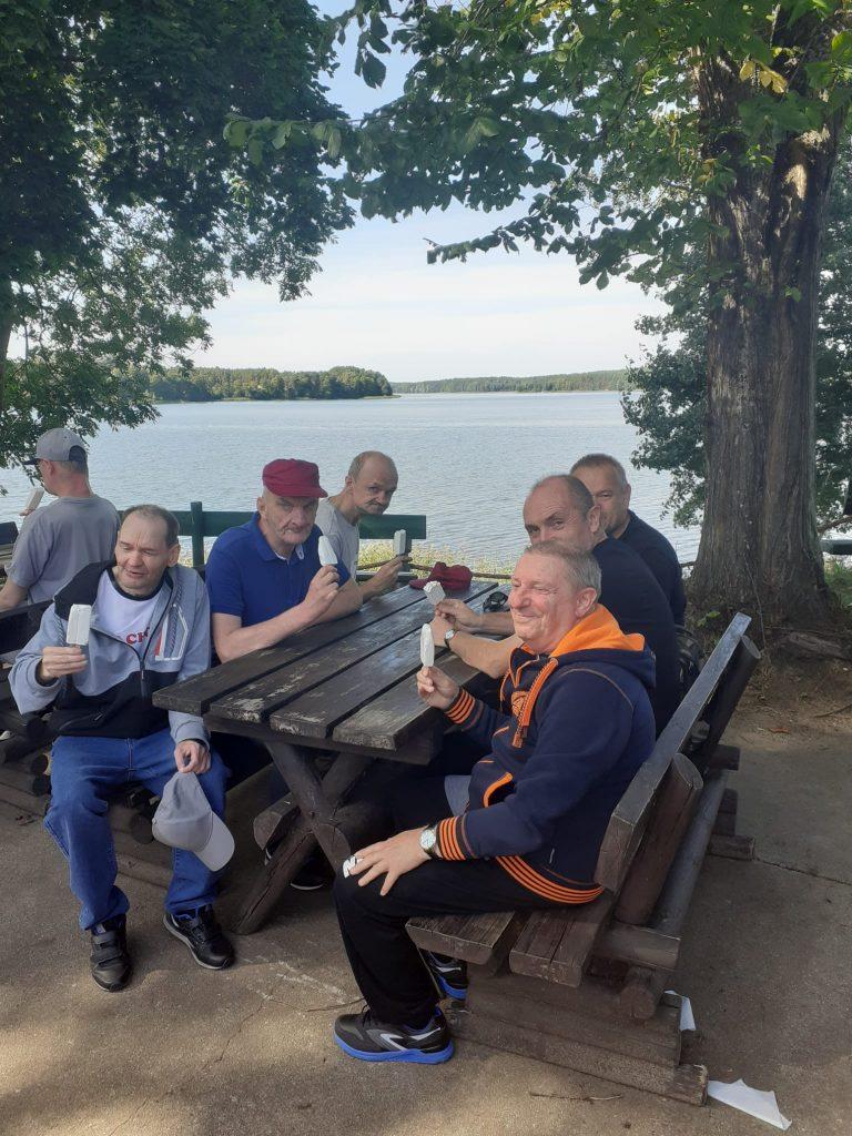Grupa mieszkańców siedząca na ławkach przy drewnianym stole, wszyscy jedzą lody na patyki w tle jezioro