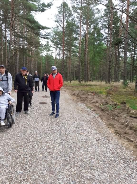 Grupa mieszkańców na spacerze w lesie. Podopieczni idą dróżką wyłożoną kamieniami. W koło las.