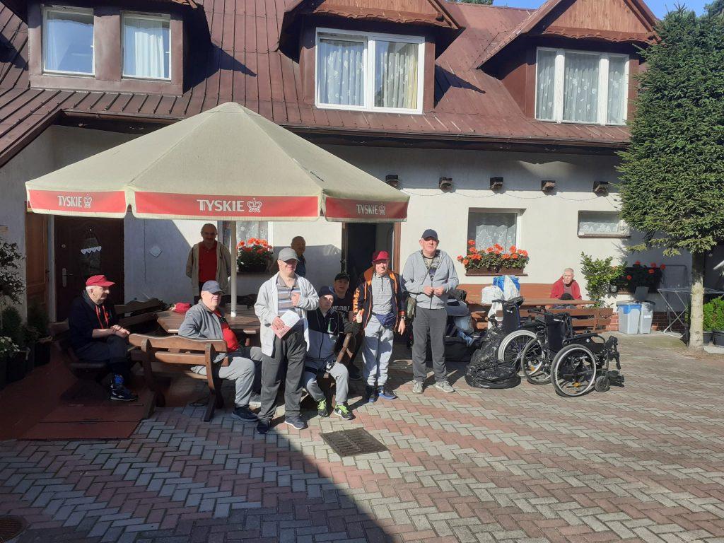Grupa mieszkańców przed budynkiem. Część stoi, część z nich siedzi na drewnianych ławkach