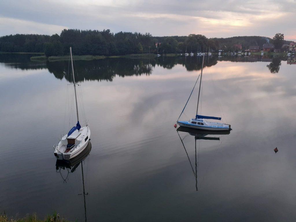Spokojna tafla wody na jeziorze... lustrzane odbicie nieba oraz lasu. Dwie łódki na jeziorze.